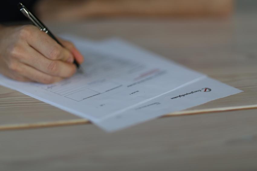 En hand som håller i en penna över en ansökningsblankett för det statliga batteristödet