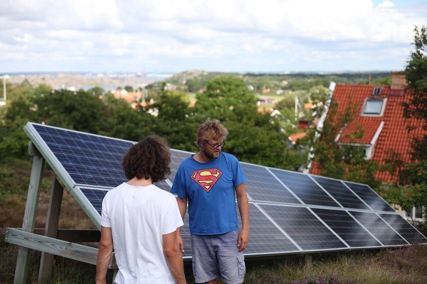 Erik Wallnér och Jörgen Larsson, iförd en Stålmannen-tröja, står vid Jörgens solcellsanläggning som han har satt upp på berghällen bakom sitt hus