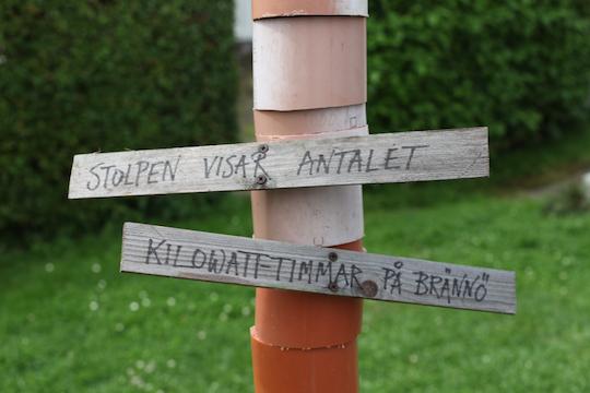 Skylten som Jörgen Larsson har satt upp utanför matbutiken på Brännö, därsolcellshushållen har satt upp varsin bit avloppsrör som representerarsolelproduktionen varjeår