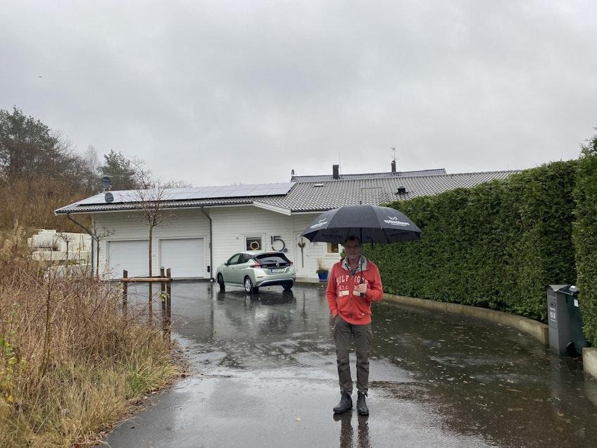 Max framför sitt hus med solpaneler och batterier