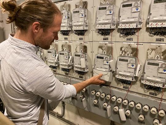 David Nordström framför de nya elmätarna på den gamla mätartavlan