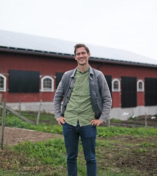 Otto Hedenmo från Länsstyrelsen i Jönköping står framför solcellsanläggningen på Sjövik gård