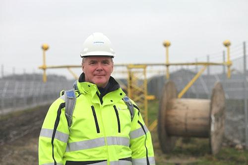 Tommy Schröder Andersen, projektledare hos Göteborg Energi, står i solcellsparken framför en landningslampa tillhörande Säve flygplats