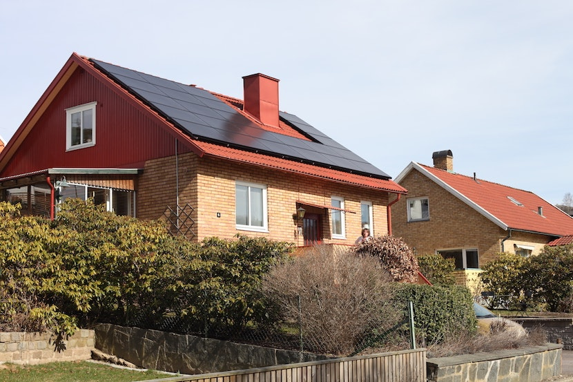 Rose-Marie framför sitt hus med nymonterade solceller på taket
