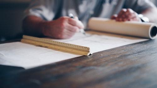 Bild på en person som ritar på ett stort pappersark