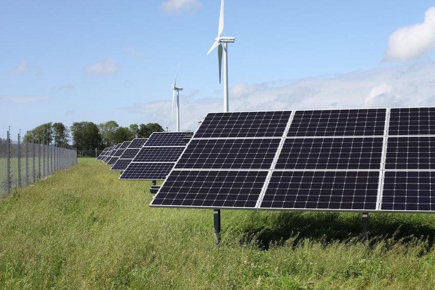 Solcellsparken Solsidan som står längs E6:an utanför Varberg, med två stora vindkraftverk bakom